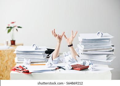 The many crumpled papers on desk of stressed male workplace