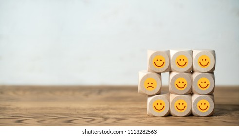 many cubes with smiling emoticons and one sad one standing out