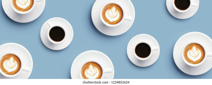 Many cups of coffee and cappuccino with latte art on blue background. Top view, banner for site.