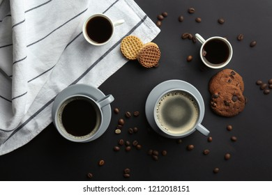 Many cups with tasty aromatic coffee and cookies on black background, flat lay