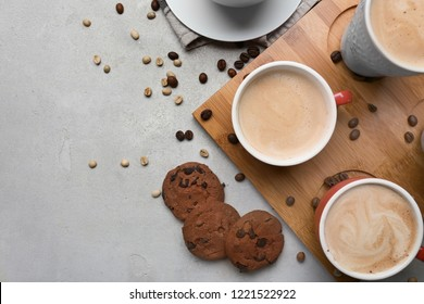 Many cups with tasty aromatic coffee and cookies on grey table