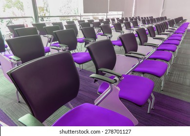 Many dark purple chairs arranged neatly in a training room.