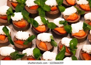 Many delicious beautiful capcakes with protein cream and fresh strawberries and mint. View from above. Concept children's birthday, sweet table, treats, banquet