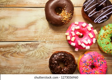Many delicious donuts on the wooden table