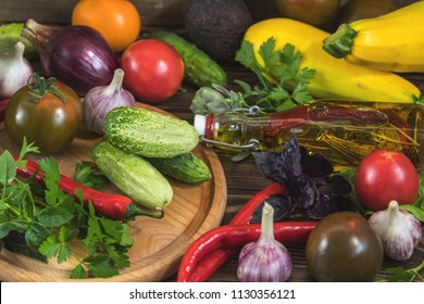 Many delicious juicy fresh colorful summer vegetables and herbs on dark wooden background. Close up, shullow depth of the field. Healthy eating concept background.