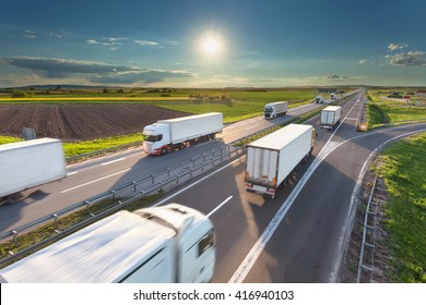 Many delivery trucks driving through agricultural fields. Fast blurred motion drive on the freeway at beautiful sunny day. Freight scene on the motorway near Belgrade, Serbia.