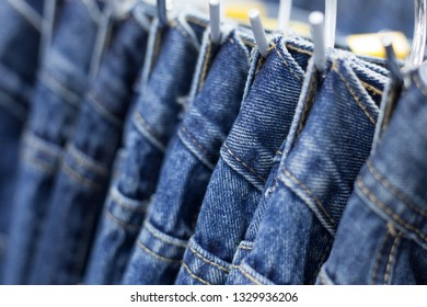 Many denim jeans hanging on a rack
