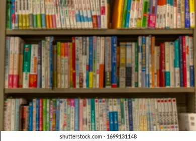 Many different books on the shelves in the store. Blurred. Background. Vertical.