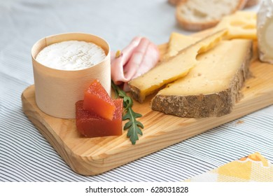 Many different cheeses over a board with a couple of slices of bread out of focus on the background