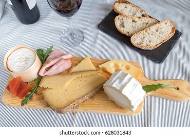 Many different cheeses over a board next to a stone board with bread and a cup of red wine in the background