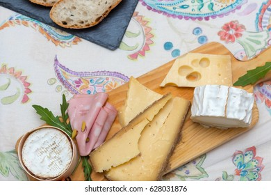 Many different cheeses over a board next to a stone board with bread