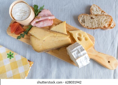 Many different cheeses over a board next to a couple of slices of bread