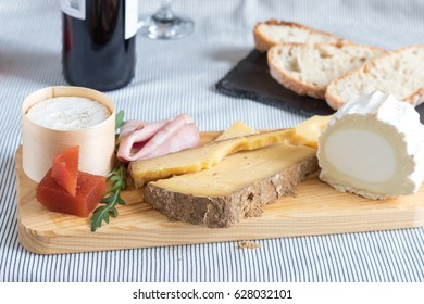 Many different cheeses over a board next to a stone board with bread and a bottle of wine in the background