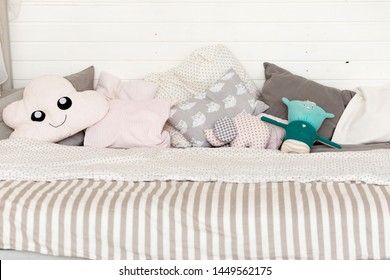 Many different children's pillows on the bed