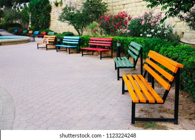 Many different color (red, blue, green, yellow) empty wooden benches in the park for romantic rest during walk, Sliema, Malta, Europe