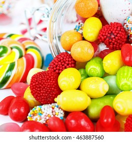 many different colorful candies and chewing gum close up on white background