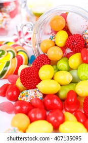 many different colorful candies, sweetmeats and chewing gum scattered on a white background with space for your text