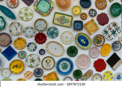 Many different and colorful plates and bowls hanging on the wall