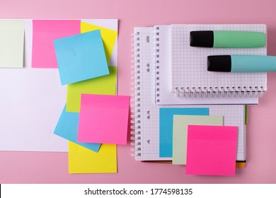 many different colorful stationary objects on pink student's or office desk