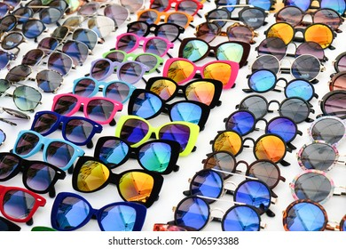 Many different colorful sunglasses in a diagonal row