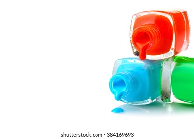 many different colors of nail Polish in bottles, and a little bit spilled on a white isolated background