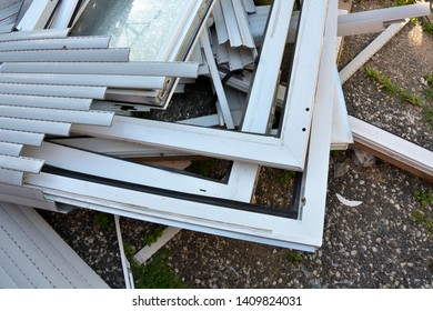 Many different construction debris from old plastic window frames of white color with glass.