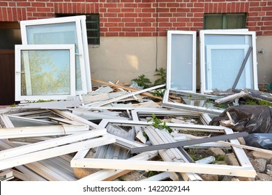 Many different construction debris from old plastic window frames of white color with glass. The concept of replacing old window frames with new ones. The concept of protecting nature from plastic.