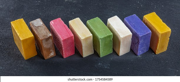 Many different handmade soap bars on black wood background.
