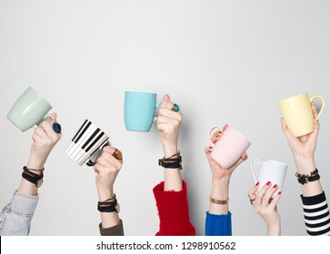 Many different hands holding coffee cups
