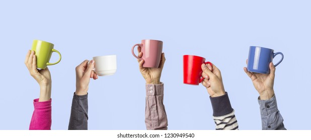 Many different hands holding multi colored cups of coffee on a blue background. Female and male hands. Concept of a friendly team, a coffee break, meeting friends, morning in the team. Banner