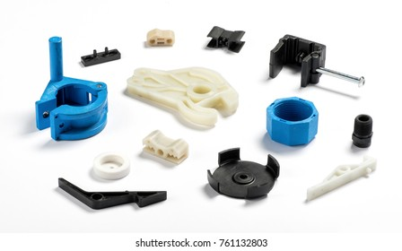 Many different injection plastic parts of white, blue and black colour spread on white background