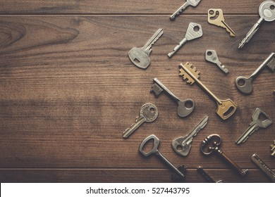 many different keys on brown wooden background with copy space