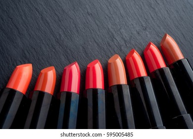 Many different lipsticks, different colors on a black background