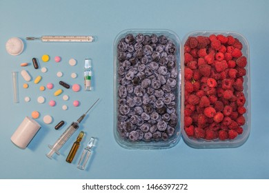Many different medications next to fresh berries. Healthy nutrition or use of chemistry. Vitamins contained in the berries next to the vitamins in tablets. Healthy food and harmful pills.