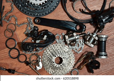 Many different metal parts and components of the running gear of a sports bike. Brake levers, sprockets, gears, pinions and many other components for bicycle assembly. Bicycle repair concept