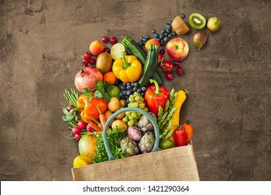 Many different multicolored vegetables and fruits falling out of canvas bag onto grey rustic background
