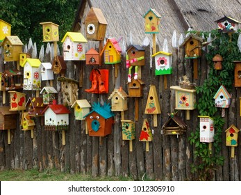 Many different shapes bird feeders birdhouse for nesting box hanging on wooden fence. Bird feeders in park. Colorful bird feeders in rustic garden. Lot of nesting boxes or houses for feeding animals