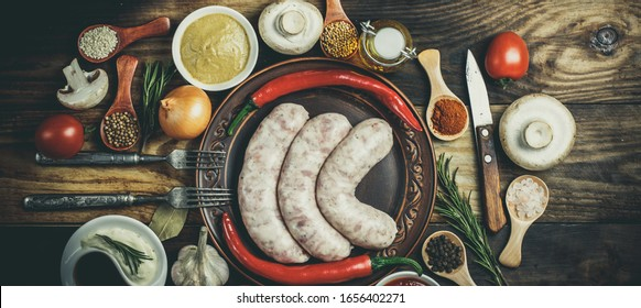 Many different spices, vegetables and ingredients, and fresh raw barbecue sausages for the family.