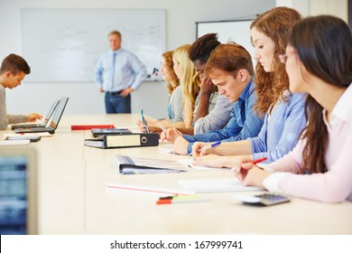 Many different students learning in a class in university