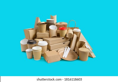 Many different take-out food containers, pizza box, coffee cups in holder and paper boxes on aqua blue background.
