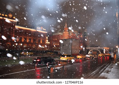 Many different taxi cars at night when it snows on Manezhnaya square. Moscow. 22.11.2018