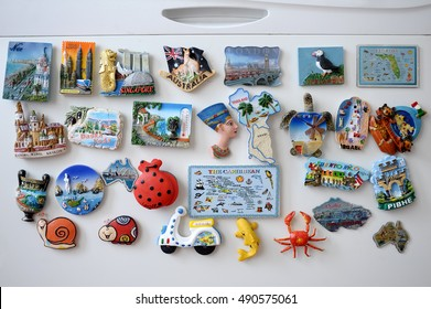 many different travel magnet souvenires on the fridge