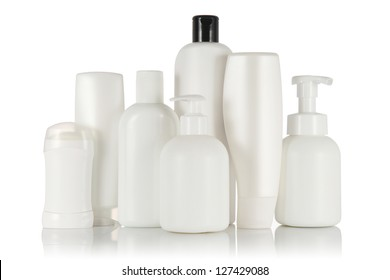 Many different white tubes and bottles for hygiene, health and beauty on a white background with reflection isolated.