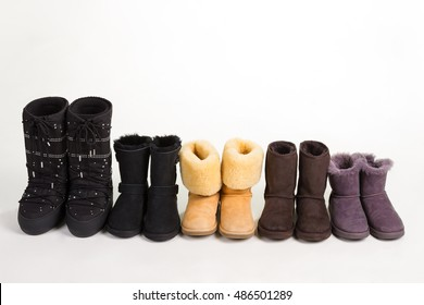 Many different winter boots on a white background. Women's shoes standing in a row.