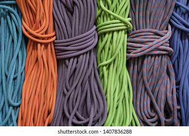 many differently colored coiled up rock climbing ropes