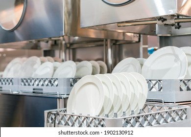 many dish or white plate arranged on basket for cleaning by automatic dishwasher machine in kitchen room restaurant