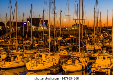 many docked boats in the harbor of blankenberge during sunset, beautiful city scenery, Belgium, 15 february, 2019