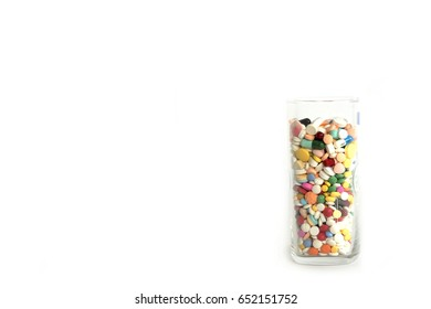 Many drug and pill fill in the glass on white background
