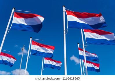 many dutch flags against a blue sky