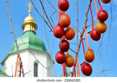 Many Easter eggs are hung on the willow branch against the Orthodox cathedral and the blue sky.